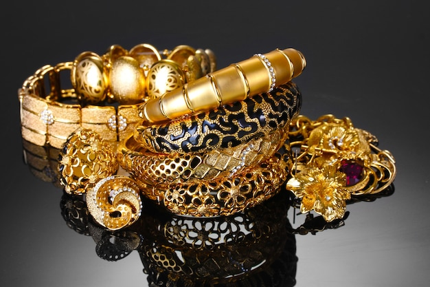 Schöne goldene armbänder, ringe und schmuck auf grauem hintergrund