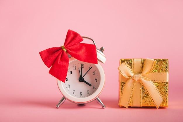 Schöne goldene box mit einer schleife und einer uhr mit einer roten schleife