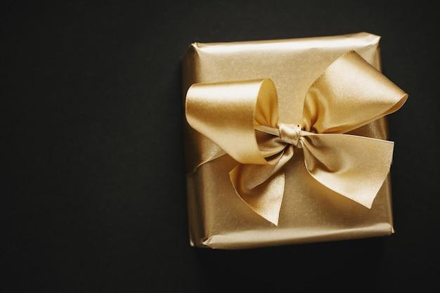 Schöne goldene box weihnachtsgeschenk mit goldenem band auf schwarz