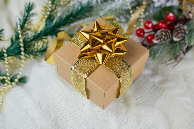 Schöne goldene geschenkbox mit einem bogen auf dem schnee für das neue jahr und weihnachten