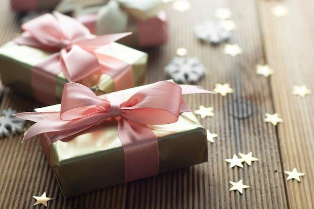 Schöne goldene geschenke weihnachten, party, geburtstagshintergrund. feiern sie shinny überraschungskästen copyspace hölzernen hintergrund