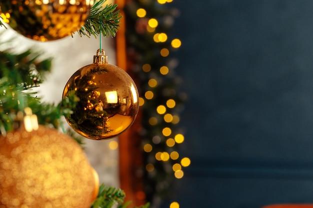 Schöne goldene kugel, die von einem weihnachtsbaum hängt