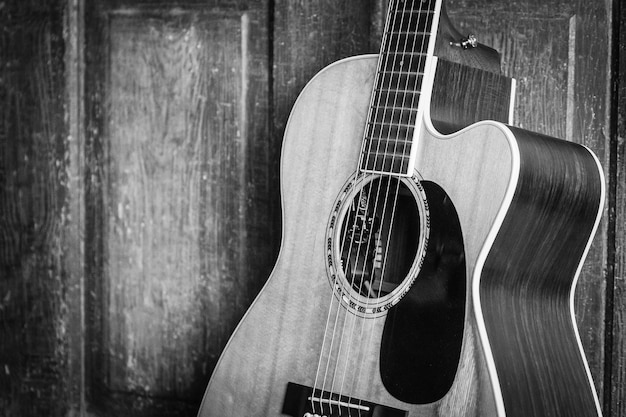 Schöne graustufenaufnahme einer akustikgitarre, die an eine holztür auf einer holzoberfläche gelehnt wird
