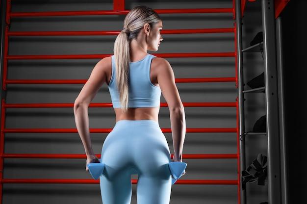 Schöne große blondine, die im fitnessstudio mit hanteln in ihren händen vor dem hintergrund der wandstange aufwirft. rückansicht.