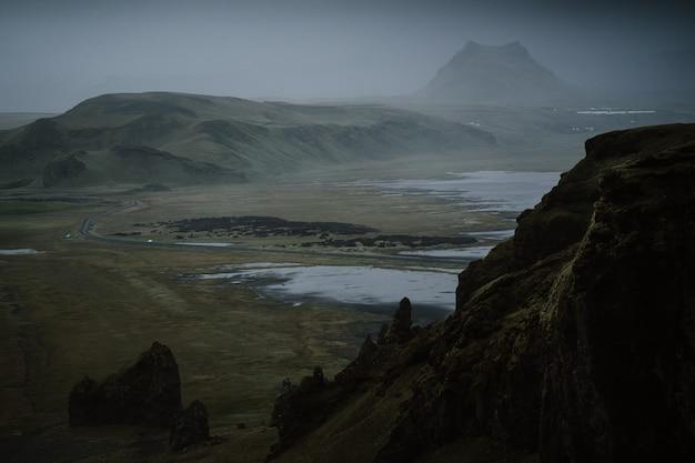 Schöne grüne landschaft mit einem see, umgeben von hohen bergen, die von nebel umhüllt sind