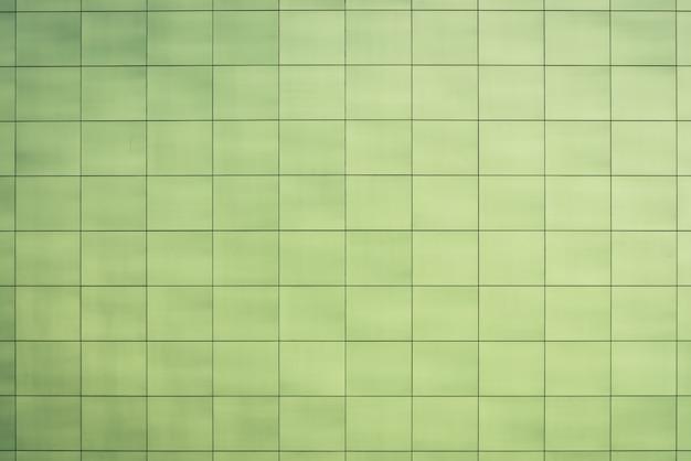Schöne grünliche toilette, küche, badezimmer - glatte quadratische fliesennahaufnahme. hellgrüne beschaffenheit der wand, boden, decke nah mit copyspace. einfache grüne glatte einfassung fliese der gebäudewand.
