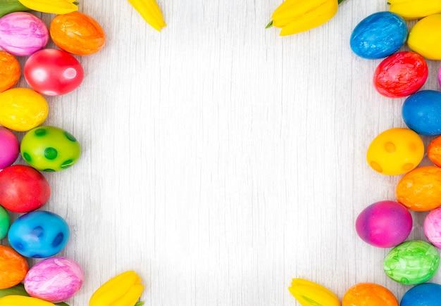 Schöne gruppe ostereier im frühling des ostertages, rote eier, blau, lila und gelb mit tulpen