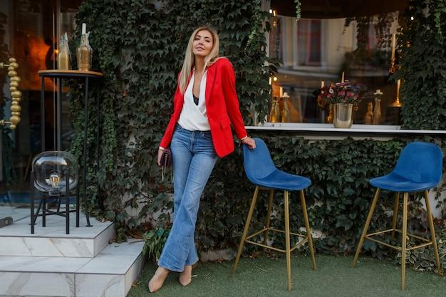 Schöne gut aussehende blonde frau in der roten jacke, die im stadtcafé aufwirft