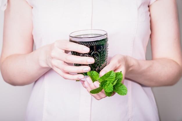 Schöne hände, die kristallglas des flüssigen chlorophyllgetränks halten