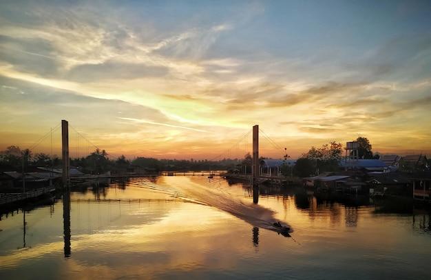 Schöne hängebrücke des hellen sonnenaufgangs der goldenen stunde, flussboot, das durch das wasser sich bewegt. motiv ist unscharf.
