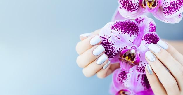 Schöne hand mit perfekter nagelrosa-maniküre und lila orchideenblume