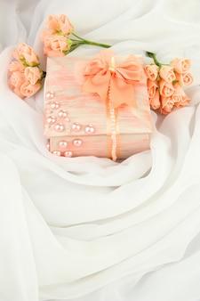Schöne handgemachte schatulle und blumen, isoliert auf weißem stoffhintergrund