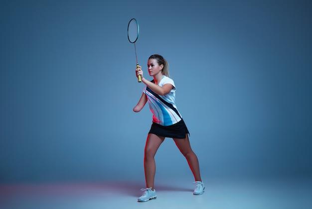 Schöne handicap-frau, die im badminton übt, isoliert auf blauem hintergrund im neonlicht. lebensstil inklusiver menschen, vielfalt und gleichberechtigung. sport, aktivität und bewegung. exemplar für anzeige.