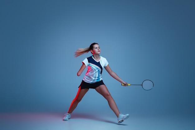 Schöne handicap-frau, die im badminton übt, isoliert auf blauem hintergrund im neonlicht