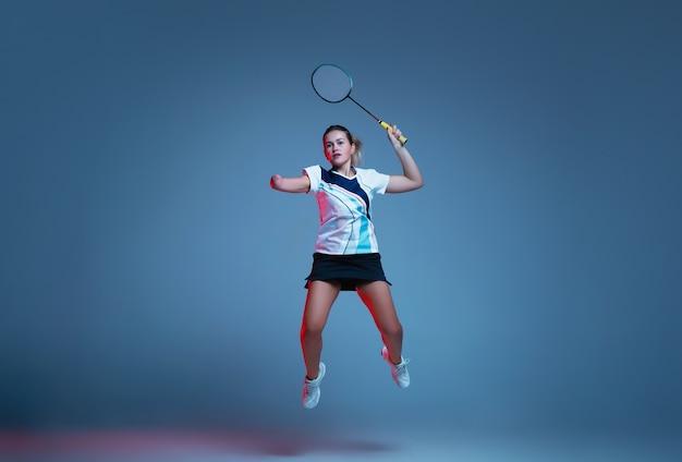 Schöne handicapfrau, die im badminton lokalisiert auf blauem hintergrund im neonlicht übt. lebensstil integrativer menschen, vielfalt und gleichheit. sport, aktivität und bewegung. copyspace für anzeige.