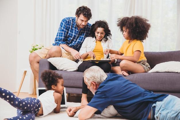 Schöne hausfamilie bleibt zusammen im wohnzimmer, vater, mutter und großvater, die mit tochter-mix-rennen spielen.