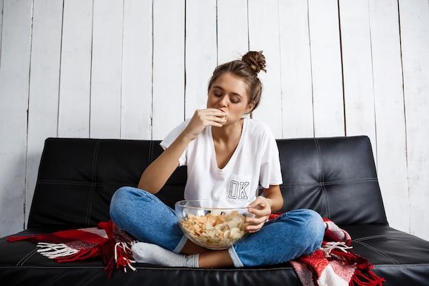 Schöne hausfrau, die chips isst, fernsieht, am sofa sitzt.