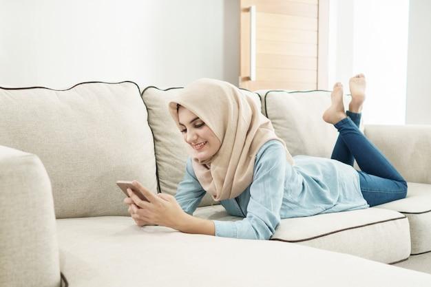 Schöne hausfrau, die hijab sms auf handy trägt, während l