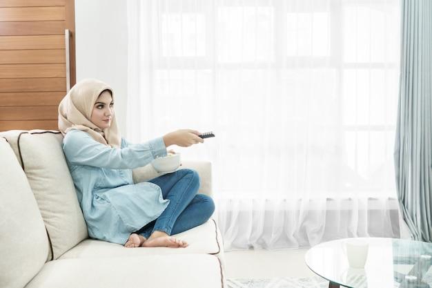 Schöne hausfrau, die hijab trägt, das fernsehen in einem leisu sieht