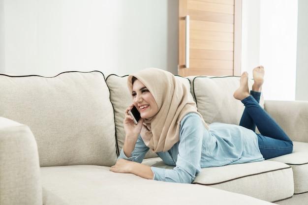 Schöne hausfrau, die hijab trägt, der auf handy spricht, während ich
