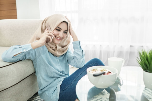 Schöne hausfrau, die hijab trägt, der auf handy spricht, während s