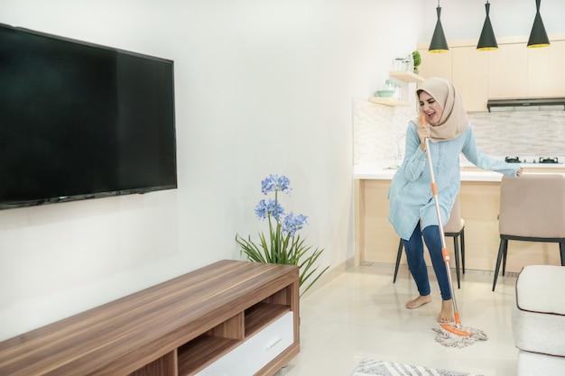 Schöne hausfrau, die hijab trägt, der ihr haus putzt