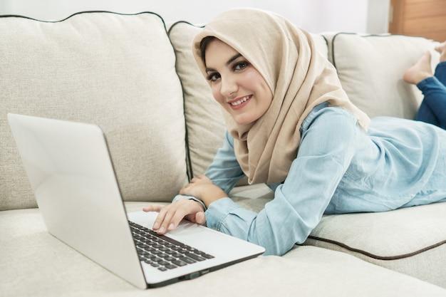 Schöne hausfrau, die hijab trägt, genießt das surfen auf laptop in einem