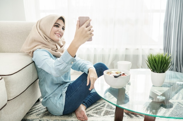Schöne hausfrau, die hijab trägt und selfies in einem freizeit-ti nimmt