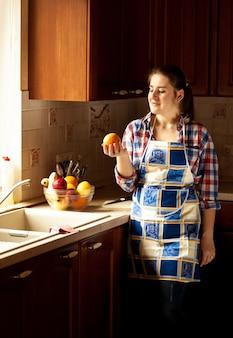 Schöne hausfrau, die orange auf der küche im landhausstil anschaut