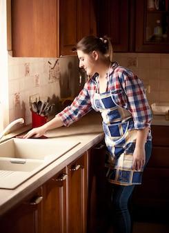 Schöne hausfrau, die tischplatte auf küche putzt