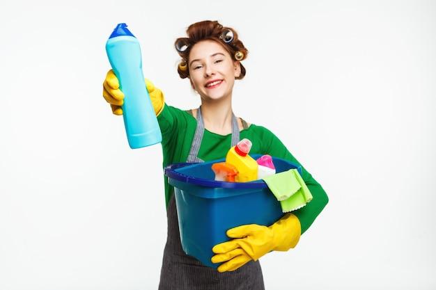 Schöne hausfrau hält reinigungswerkzeuge und zeigt flasche