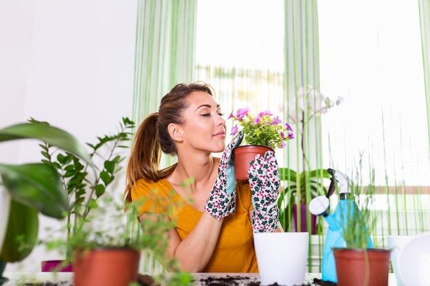 Schöne hausfrau mit blume im topf und gartenset. zuhause arbeiten. blumen pflanzen und frühjahrsputz.