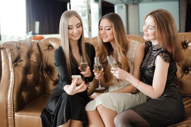 Schöne heiße mädchen, die parteispaß, trinkender champagner haben