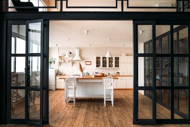 Schöne helle küche mit großem tisch und barhockern und weißen möbeln mit breiten schwarzen glastüren.