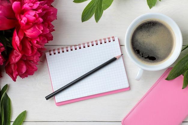 Schöne helle rosa blumenpfingstrosen und ein notizbuch mit einer tasse kaffee auf einem weißen hölzernen hintergrund. ansicht von oben.