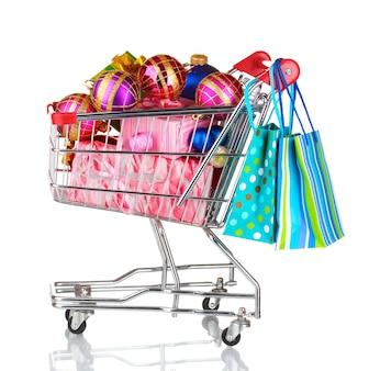 Schöne helle weihnachtskugeln und geschenke im warenkorb und papiertüten isoliert auf weiß