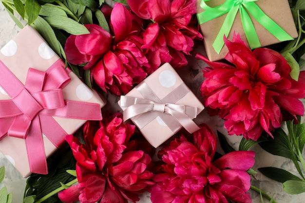 Schöne hellrosa blüten von pfingstrosen und eine geschenkbox auf hellem betonhintergrund. ansicht von oben.