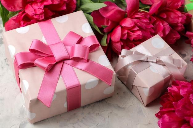Schöne hellrosa blüten von pfingstrosen und eine geschenkbox auf hellem betonhintergrund.