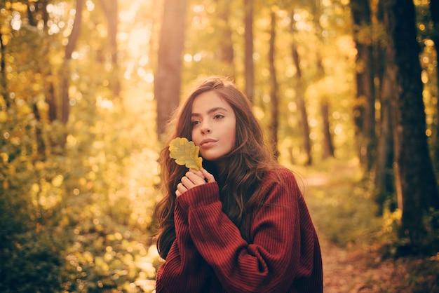 Schöne herbstfrau mit herbstlaub auf fallnaturhintergrund. hallo herbst. atmosphärisches modefoto im freien der jungen schönen dame in der herbstlandschaft