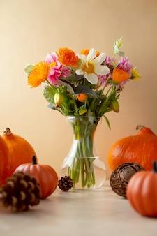 Schöne herbstkomposition mit blumenstrauß in vase und kürbissen, warme und gemütliche kulisse des herbstes