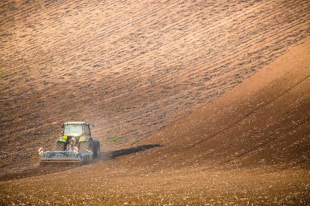 Schöne herbstlandschaft mit arbeitendem traktor in südmähren, tschechische republik,