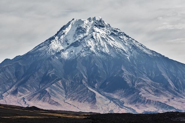 Schöne herbstliche vulkanische landschaftsansicht des schneebedeckten kegels des stratovulkans