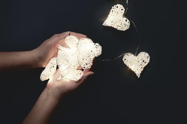 Schöne herzförmige lichterketten, die in den händen leuchten. valentinstag