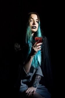 Schöne hexe mit blutigem becher