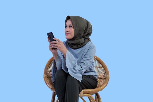 Schöne hijab-frau, die auf dem stuhl sitzt, hält das telefon und schaut mit einer hoffnung auf