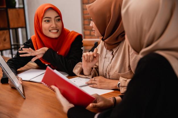 Schöne hijab-frau, die lächelt, wenn sie mit ihren universitätsfreunden plaudert