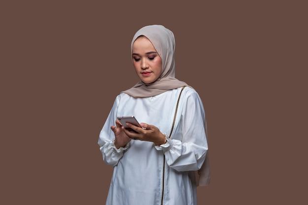 Schöne hijab-frau tippt eine nachricht auf ihrem handy, die auf einfarbigem hintergrund isoliert ist