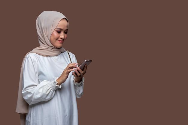 Schöne hijab frau tippt eine nachricht auf ihrem handy mit lächeln ausdruck