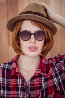 Schöne hippie-frau in einem hut und in einer sonnenbrille