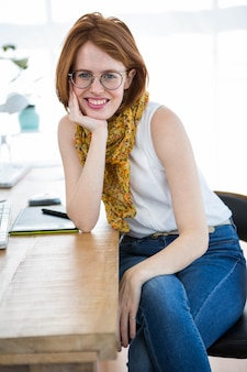 Schöne hippie-geschäftsfrau, die in ihrem büro, lehnend auf ihrem schreibtisch sitzt
